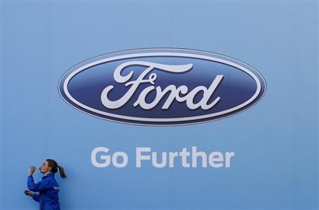 A woman has a drink as she walks past a logo of carmaker Ford at the entrance to a media event for the launch of a concept car in Sydney August 13, 2013. REUTERS/Daniel Munoz