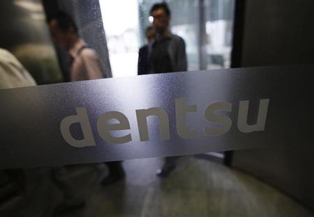 The logo of Dentsu Co. is seen at the entrance of the company headquarters in Tokyo July 12, 2012. REUTERS/Issei Kato