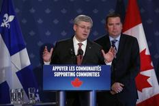 Canada's Prime Minister Stephen Harper (L) gestures as he speaks during a news conference at the Lac-Megantic Golf Club in Frontenac, November 21, 2013. REUTERS/Mathieu Belanger