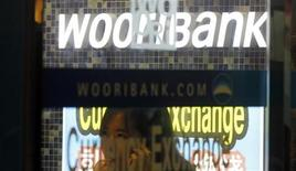 A woman uses her mobile phone at a branch of Woori Bank in Seoul August 17, 2011. REUTERS/Lee Jae-Won