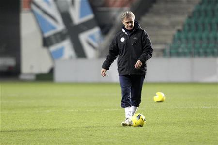 Estonia's national soccer team head coach Tarmo Ruutli plays with the ball as he attends a training session in Tallinn November 10, 2011. REUTERS/Ints Kalnins