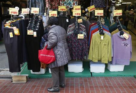An elderly woman looks at clothes at a shop in Tokyo's Sugamo district, an area popular among Japanese elderly, February 4, 2013. REUTERS/Yuya Shino