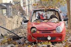 Люди фотографируют место взрыва нефтепровода компании Sinopec Corp в городе Циндао, КНР 22 ноября 2013 года. Взрыв на одном из принадлежащих китайской нефтяной компании Sinopec Corp нефтепроводов в городе Циндао унес в пятницу жизни 22 человек, порт Циндао остановил работу, сообщили китайские СМИ и брокеры в порту. REUTERS/Stringer