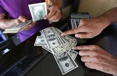 A money changer sells U.S. dollars to a customer in the border city of Hatay September 17, 2013. REUTERS/Umit Bektas