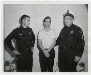 Lee Harvey Oswald, accused of assassinating former U.S. President John F. Kennedy, is pictured with Dallas police Sgt. Warren (R) and a fellow officer in Dallas, in this handout image taken on November 22, 1963. REUTERS/Dallas Police Department