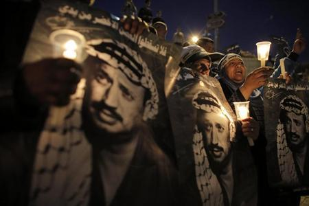 Palestinians hold candles and posters depicting late Palestinian leader Yasser Arafat during a rally marking the 9th anniversary of his death near Damascus Gate in Jerusalem's Old City November 11, 2013. REUTERS/Ammar Awad
