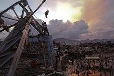 Survivors place a makeshift flag over a sports hall destroyed by Typhoon Haiyan, in Tacloban November 20, 2013. REUTERS/Damir Sagolj