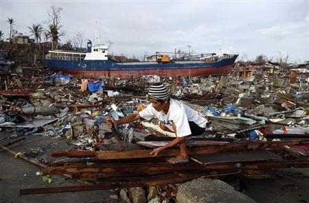 A typhoon survivor retrieves nails from planks to build a makeshift shelter, near a ship that was swept on land by super Typhoon Haiyan two weeks ago, in the typhoon battered Tacloban city, central Philippines November 22, 2013. REUTERS/Erik De Castro