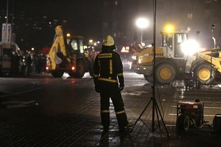 A firefighter watches the rescue operation at the site of the collapsed Maxima supermarket in Riga November 21, 2013. REUTERS/Ints Kalnins