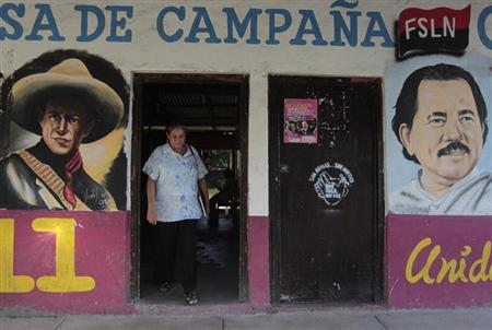 A woman walks past murals of Nicaragua's President Daniel Ortega (R) and Nicaraguan revolutionary and Sandinista leader Augusto Cesar Sandino in Catarina November 4, 2013. REUTERS/Oswaldo Rivas