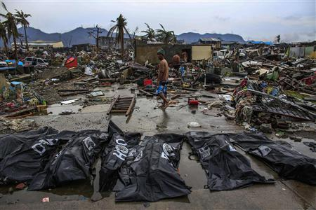 People walk past body bags in Tacloban November 23, 2013. REUTERS/Athit Perawongmetha