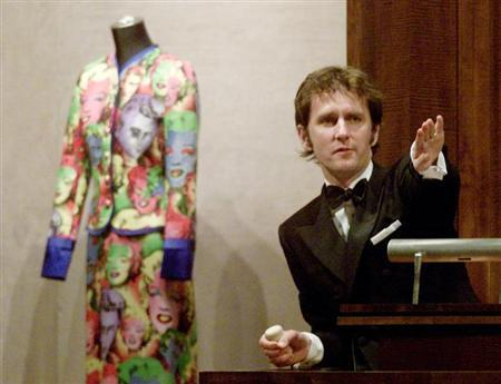 Auctioneer Tobias Meyer takes bids on a three-piece screen-printed ensemble comprising a body suit, jacket and fourreau, printed in eleven colors; by late designer Gianni Versace during an auction of furnishings and art from his Miami home at Sotheby's in New York, April 5, 2001. REUTERS/Reuters Photographer