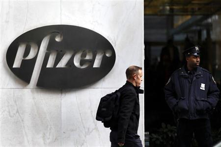 A man walks past the Pfizer logo next to a New York Police Officer standing outside Pfizer's world headquarters in New York November 5, 2013. REUTERS/Adam Hunger