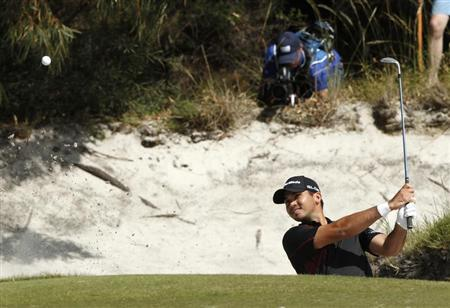 Australia's Jason Day plays a shot from a green side bunker during the final round of the World Cup of Golf at The Royal Melbourne Golf Club in Melbourne November 24, 2013. REUTERS/Brandon Malone