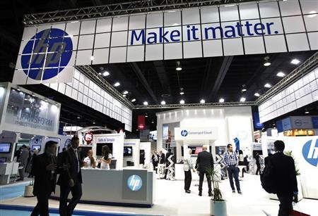People walk past a Hewlett-Packard (HP) stand during the Gulf Information and Technology Exhibition (GITEX) at the Dubai World Trade Centre in Dubai October 14, 2012. REUTERS/Jumana ElHeloueh