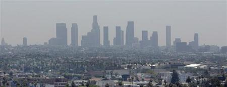 The skyline of downtown Los Angeles through a layer of smog is seen in the distance from a rooftop in Hollywood, California, May 31, 2006. REUTERS/Fred Prouser/Files