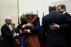 Госсекретарь США Джон Керри (третий справа) обнимает комиссара ЕС по внешней политике Кэтрин Эштон в здании ООН в Женеве 24 ноября 2013 года. Иран и шесть ведущих стран мира договорились о сворачивании ядерной программы Тегерана в обмен на частичную отмену санкций, что может расцениваться как начало сближения между Исламской республикой и Западом. REUTERS/Denis Balibouse