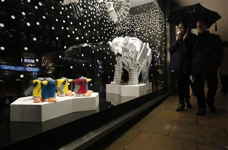 People look at animal sculptures made using household goods in the window of department store John Lewis for the Christmas season in London November 8, 2013. REUTERS/Luke MacGregor