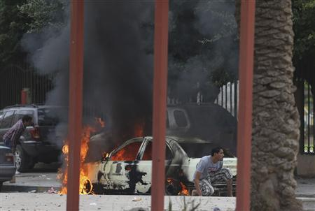 Residents hide near a burning car during clashes between members of Islamist militant group Ansar al-Sharia and a Libyan army special forces unit in the Ras Obeida area in Benghazi November 25, 2013. REUTERS-Esam Omran Al-Fetori