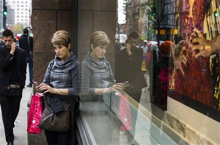A woman stops to use her phone in front of holiday window displays at Macy's flagship store in New York, November 22, 2013. REUTERS/Lucas Jackson