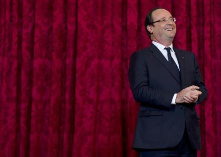 France's President Francois Hollande reacts during a ceremony where he named French singer and actress Line Renaud a ''Grand Officier de la Legion d'Honneur'' at the Elysee Palace in Paris, November 21, 2013. REUTERS/Gonzalo Fuentes