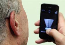 Funcionário da GN, a quarta maior fabricante de aparelhos auditivos do mundo, demonstra o uso do ReSound LiNX em Viena. A pequena Dinamarca, com menos de 6 milhões de pessoas, fornece metade dos aparelhos auditivos do mundo, e fabricantes locais do produto querem aumentar a liderança conforme a geração dos baby boomers e a do iPhone envelhecem. 22/11/2013 REUTERS/Heinz-Peter Bader