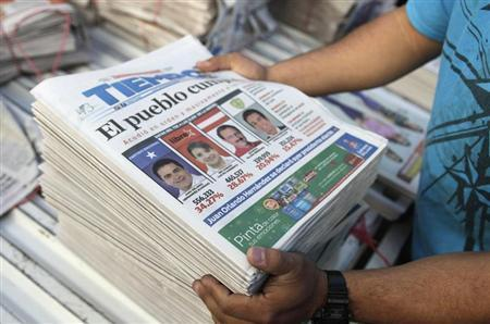 A vendor arranges newspapers covering the preliminary tally of presidential candidates Juan Orlando Hernandez of the National Party and Xiomara Castro of the Liberty and Refoundation Party (LIBRE) on the front page, in Tegucigalpa November 25, 2013. REUTERS/Jorge Cabrera