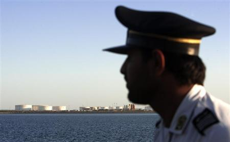 EDITORS' NOTE: Reuters and other foreign media are subject to Iranian restrictions on leaving the office to report, film or take pictures in Tehran. A security personnel looks on at oil docks at the port of Kalantari in the city of Chabahar, 300km (186 miles) east of the Strait of Hormuz January 17, 2012. REUTERS/Raheb Homavandi