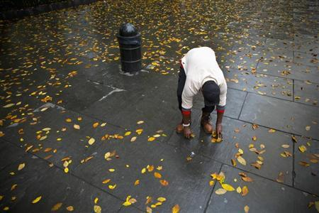 A man attempts to clean fallen leaves from a section of sidewalk in New York November 1, 2013. Strong rain and winds hit the region this morning as a storm front moved through. REUTERS/Andrew Kelly