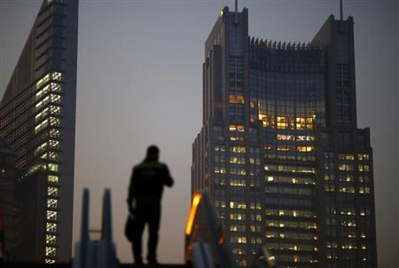 A man stands on an escalator in the financial district of Pudong in Shanghai November 20, 2013. REUTERS/Carlos Barria