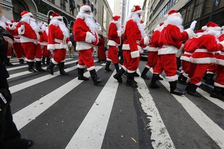 Santas cross the street while marching through Midtown Manhattan during the Volunteers of America's 110th Annual Sidewalk Santa Parade in New York November 23, 2012. REUTERS/Brendan McDermid