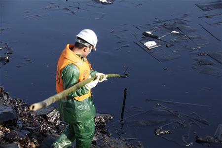 A worker cleans up leaked oil after last week's explosion of a Sinopec Corp oil pipeline in Huangdao, Qingdao, Shandong Province November 25, 2013. REUTERS/Aly Song