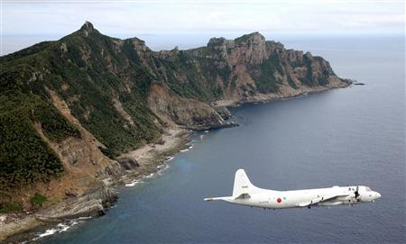 Japan Maritime Self-Defense Force's PC3 surveillance plane flies around the disputed islands in the East China Sea, known as the Senkaku isles in Japan and Diaoyu in China, in this October 13, 2011 file photo. REUTERS/Kyodo/Files