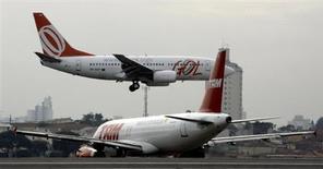 Um Airbus A320 da TAM realiza o taxiamento para decolar conforme um Boing 737 da Gol pousa na pista do aeroporto de Congonhas, em São Paulo. A demanda por voos domésticos no Brasil cresceu 4,19 por cento em outubro ante igual período de 2012, no mês considerado o início da alta temporada de fim de ano, informou a Agência de Nacional de Aviação Civil (Anac) nesta terça-feira. 27/07/2007 REUTERS/Rickey Rogers