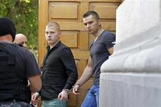 Eugen Darie (C) and Radu Dogaru (R), suspects charged with stealing paintings from a Dutch museum, are escorted by police as they leave a court building handcuffed after the first hearing in their trial in Bucharest August 13, 2013. REUTERS/Bogdan Cristel