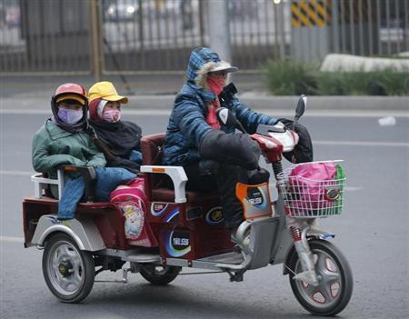 A woman and her children wearing masks ride a vehicle during a smoggy day in Beijing October 28, 2013. REUTERS/Kim Kyung-Hoon