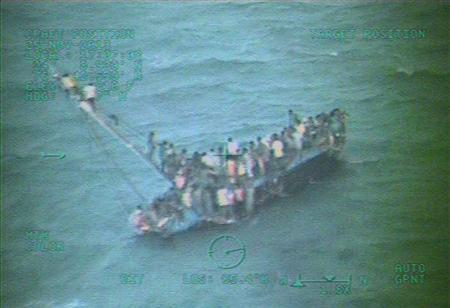 Approximately 100 Haitians sit on the hull of a sail freighter after it grounded and capsized 15 nautical miles southwest of Staniel Cay, Bahamas, November 26, 2013. REUTERS-U.S. Coast Guard photo-Handout via Reuters