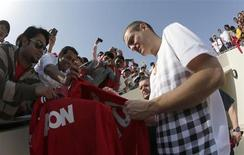 Manchester United's Nemanja Vidic signs autographs for fans before a training session at the Aspire Academy for Sports Excellence in Doha January 22, 2013. REUTERS/Fadi Al-Assaad