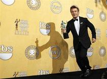 "Actor Alec Baldwin runs backstage with his award for outstanding performance by a male actor in a comedy series for ""30 Rock"", at the 18th annual Screen Actors Guild Awards in Los Angeles, California January 29, 2012. REUTERS/Mike Blake"