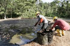 Oil workers clean up a contaminated pool in Taracoa December 10, 2007. REUTERS/Guillermo Granja