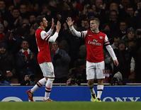 Arsenal's Jack Wilshere (R) celebrates with team mate Mesut Ozil after scoring a goal against Olympique Marseille during their Champions League soccer match at the Emirates stadium in London November 26, 2013. REUTERS/Eddie Keogh