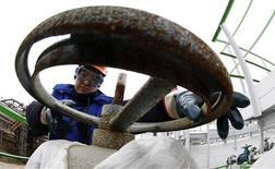 Los futuros del petróleo Brent cayeron en una sesión volátil el martes, ya que los inversionistas esperaban nuevos datos tras concluir que el acuerdo entre Irán y seis potencias mundiales no traerá un incremento inmediato al suministro de crudo del socio de la OPEP. En la foto de archivo, un trabajador en la refinería rusa de Bashneft - Novoil en Ufa. Abril 11, 2013. REUTERS/Sergei Karpukhin
