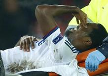 Chelsea's Samuel Eto'o grimaces as he is carried off injured during his team's Champions League Group E soccer match against FC Basel at St. Jakob-Park in Basel November 26, 2013. REUTERS/Ruben Sprich