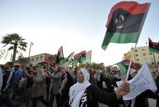 Участнии акции протеста против нападений боевиков приветствуют служащих ливийской армии в Бенгази 8 ноября 2013 года. Цены на нефть Brent держатся вблизи $111 за баррель из-за продолжающихся беспорядков в Ливии, но неожиданно резкое повышение запасов нефти в США сдерживает рост цен. REUTERS/Esam Omran Al-Fetori