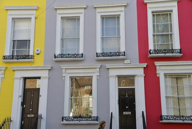 A woman walks along a residential street in Notting Hill in central London October 8, 2013. REUTERS/Toby Melville