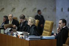 O juiz Roberto Barroso ouve durante uma sessão do julgamento do mensalão no STF, em Brasília. O fundo de pensão dos funcionários da Caixa Econômica Federal, Funcef, avalia que terá impacto pequeno caso o Supremo Tribunal Federal (STF) tome decisão favorável aos poupadores no julgamento que deve ter início nesta quarta-feira. 05/09/2013 REUTERS/Ueslei Marcelino