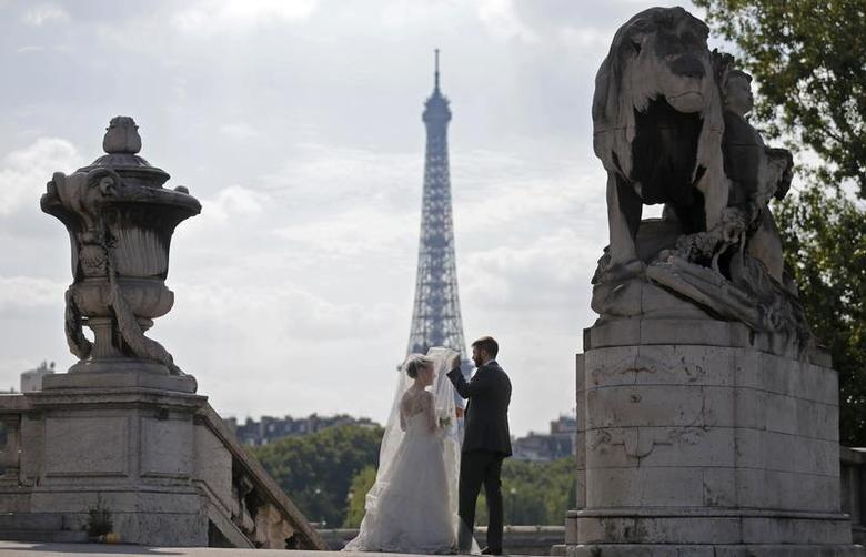 A wedding couple pose for their own photographer on the Alexandre III bridge with the Eiffel Tower in the background in Paris, August 30, 2013. REUTERS/Christian Hartmann