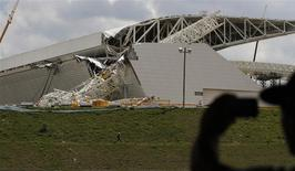 "A man takes a picture of a crane that collapsed on the site of the Arena Sao Paulo stadium, known as ""Itaquerao"", which will host the opening soccer match of the 2014 World Cup, in Sao Paulo November 27, 2013. REUTERS/Nacho Doce"