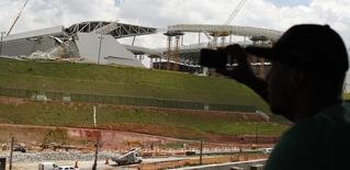 Homem tira foto de acidente no estádio do Corinthians, que está em construção na zona leste de São Paulo. Um guindaste caiu nesta quarta-feira sobre parte da estrutura do estádio que vai abrir a Copa do Mundo de 2014, deixando dois mortos e provocando preocupação sobre possível atraso nas obras para o torneio de junho. 27/11/2013 REUTERS/Nacho Doce