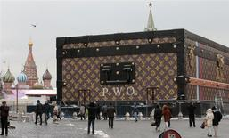 People walk past a Louis Vuitton pavilion which is in the shape of a giant suitcase, as the St. Basil's Cathedral (L) and the Spasskaya Tower are seen in the background, in central Moscow, November 27, 2013. REUTERS/Tatyana Makeyeva